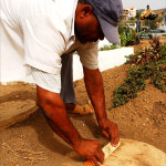 Cleaning dirt off Hebrew tombstone of Abraham Benros
